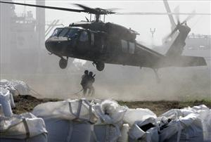 Members of the Louisiana National Guard hook a sandbag to a helicopter in Port Fourchon, La., May 11, 2010. Helicopters are dropping sandbags at the mouths of marshes.