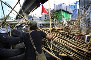 Red Shirt activists stand guard at their barricade in Bangkok yesterday.