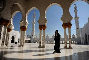 ABU DHABI, UNITED ARAB EMIRATES - DECEMBER 19: A woman strolls the Sheikh Zayed Mosque on December 19, 2009 in Abu Dhabi, United Arab Emirates. The Mosque, named after Sheikh Zayed bin Sultan Al Nahyan, is the biggest mosque in the United Arab Emirates.