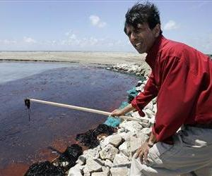 Louisiana Gov. Bobby Jindal displays a stick that he dipped into oil on a land bridge built by the Louisiana National Guard to protect wetlands on Elmer's Island in Grand Isle, La., May 20, 2010.