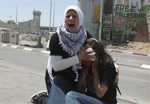 A Palestinian woman reacts as she holds a cloth to the bleeding face of an American activist who was wounded during clashes with Israeli troops between Ramallah and Jerusalem, Monday, May 31, 2010.