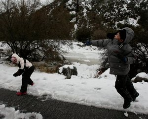 Children play with snow on the side of the road in the community of Mount Baldy, Calif., north of Claremont, Friday, Jan. 25, 2008. A powerful storm dumped snow and rain as it moved across California Wednesday, shutting down a major interstate highway and prompting flood watches in areas scarred...