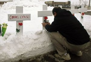 Greg Zanis, of Sugar Grove, Ill., puts up five crosses and leaves flowers in front of the Lane Bryant store at the Brookside shopping center in Tinley Park, Ill., Sunday, Feb. 3, 2008. A gunman fatally shot five people at a store in a suburban Chicago strip mall and fled...