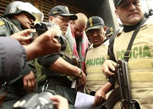 Joran van der Sloot, center, is escorted by police officers before being transported in a police car in Lima, last week.
