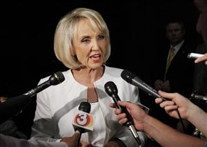 Arizona Gov. Jan Brewer answers questions from the media in Phoenix.