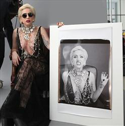 In this publicity image released by Polaroid, Lady Gaga poses with a large Polaroid picture of herself at the MIT Art Museum in Cambridge, Mass. The photo will become a part of the Museum's Polaroid archive.