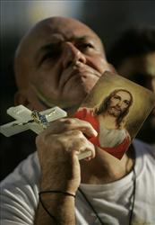 A fan of Brazil's soccer team holds a cross and an image of Jesus while watching a match.