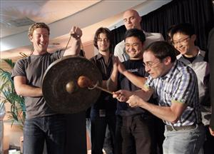 Ben Gerzfield hits a gong as Facebook CEO Mark Zuckerberg holds it to launch the social network site's new Places feature during a press conference in Palo Alto, Calif., on Wednesday, Aug. 18, 2010.