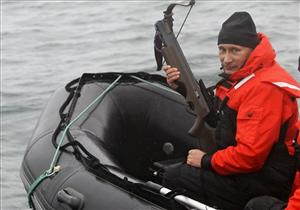 Russian Prime Minister Vladimir Putin holds a crossbow as he sits on a rubber boat at the Olga Harbor of Kamchatka Peninsula.