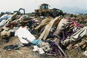 In this Sunday, July 31, 1994 file picture, a bulldozer operated by a French soldier shovels bodies into a mass grave at the Kibumba refugee camp in Rwanda near Goma, Zaire.