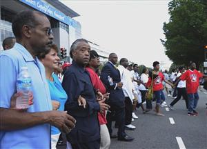 Rev. Al Sharpton, third from left, and others march through Washington Saturday.