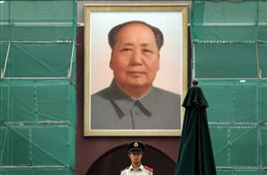 A Chinese paramilitary policeman stands guard in front of a portrait of Mao Zedong hanging on Tiananmen Gate.