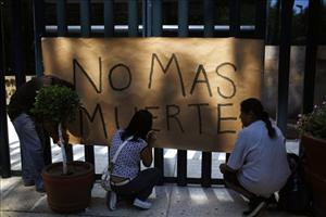 People hang a banner that reads in Spanish No more death outside the federal attorney general office in commemoration of Day of the Dead in Mexico City, Monday Nov. 1, 2010.