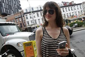 Jill Small, of Los Angeles, holds her iPhone 4 during an interview with the Associated Press,  Friday, July 16, 2010 in New York.