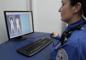 A TSA officer checks body scans on a computer screen as volunteers go through the first full body scanner installed at O'Hare International Airport.