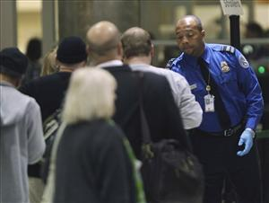 A TSA official checks passengers entering a security checkpoint.