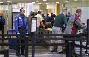 TSA Transportation Security Officers, in blue uniforms, check airline passenger as they check-in at Washington's Ronald Reagan National Airport, Monday, Nov. 15, 2010.