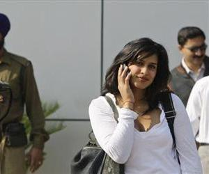 An Indian paramilitary officer, left, and an air passenger talk on their cell phones in this file photo.