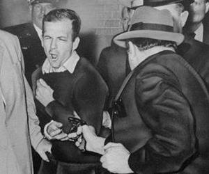 Lee Harvey Oswald reacts as Dallas night club owner Jack Ruby, foreground, shoots at him from point blank range in a corridor of Dallas police headquarters, Nov. 24, 1963.