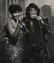 In this Jan. 11, 1987 file photo, soul singers James Brown and Aretha Franklin sing during a Home Box Office taping at the Taboo night club in Detroit.
