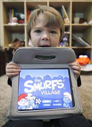 In this photo taken Dec. 7, 2010, a young boy has the Smurf's Village on an iPad.