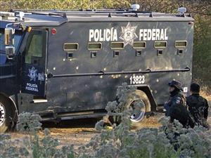 Federal agents stand next to a truck riddled with bullets in Apatzingan, Mexico, Friday Dec. 10, 2010. At least eleven people have been killed including La Familia leader Nazario Moreno Gonzalez.
