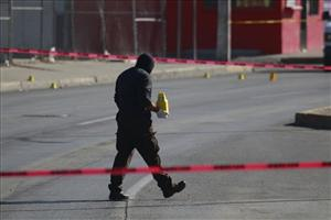 An investigator places evidence markers at the site where a man was shot to death in the northern border city of Ciudad Juarez, Mexico, Thursday Dec. 9, 2010.