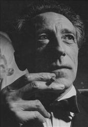Jean Cocteau , French novelist and filmmaker, smokes a cigarette at the 'Bal des Petits Lits Blancs', where Cocteau was Master of Ceremonies, in Paris, France, October 1948.