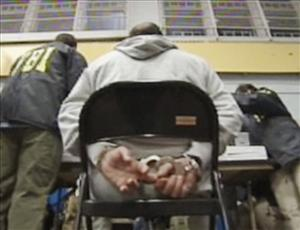 In this frame grab taken from Associated Press Television News video, a suspect sits handcuffed Thursday in Brooklyn.