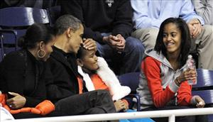President Barack Obama kisses his daughter Sasha on the head while his other daughter Malia, right, and first lady Michelle Obama look on.