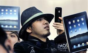 A Japanese customer uses his iPhone as he waits to buy an iPad in Tokyo.