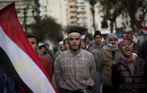 Anti-government protesters shout slogans as they line up this morning after spending the night in front of the Egyptian Parliament in Cairo.