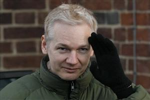 Julian Assange gestures as he gets back into a car at Beccles Police Station in Suffolk, England.