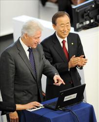 Former US President Bill Clinton (L) and United Nations Secretary General Ban Ki-Moon (R) test software on a computer March 4, 2010.
