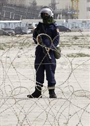 A riot police officer stands behind a barbed wire barricade near the Pearl roundabout in Manama, Bahrain, early Thursday morning, Feb. 17, 2011.