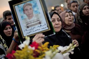 An woman holds a photo of a boy at a memorial in honor of those who died in the Egyptian uprising.