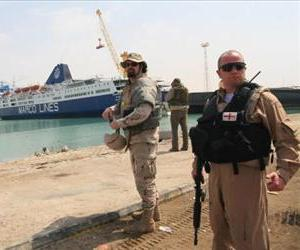 An armed Private Security Detail (PSD) with the London based AEGIS security company, guards US contractors overseeing the delivery of vehicles to Iraqi security forces, April 26, 2008.