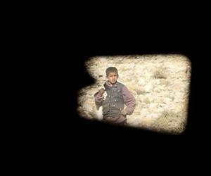 An Afghan boy looks on as US soldiers patrol in an armored vehicle near Badel Combat Out Post in Kunar province in eastern Afghanistan, in this Jan 3, 2011 file photo.