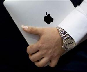 A woman wearing a watch holds an iPad at the CeBIT IT fair on its opening day on March 1, 2011 in Hanover, central Germany.