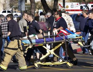Emergency personnel and Daniel Hernandez, an intern for Gabrielle Giffords, move Giffords after she was shot in the head outside a shopping center in Tucson, Ariz. on Saturday, Jan. 8, 2011.