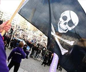 A demonstrator waves a Jolly Roger while Sweden's Pirate Party chairman and founder Rickard Falkvinge talks in the background, in Stockholm, Sweden, April 18 2009.