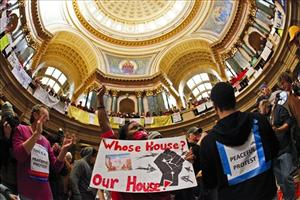 In this Feb . 19, 2011 file photo, Neporsha Hamlin, center, of Madison, Wis, protests the governor's budget bill at the State Capitol in Madison.