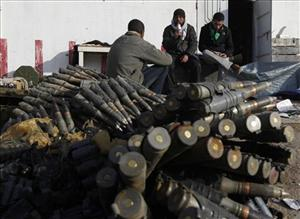 Libyan rebels sit next to munitions in Brega, eastern Libya, on Saturday.