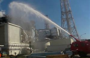 A fire engine sprays water toward reactor No. 3 of the Fukushima Dai-ichi nuclear complex.