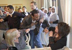 FT journalist Charles Clover, center top, attempts to stop a Libya Ministry of Information official from grabbing Iman Al-Obeidi, bottom right.