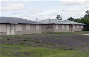 In this May 19, 2009, photo, a pair of boarded up duplexes sit empty in Lehigh Acres, Fla.