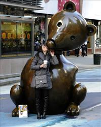 A tourist kisses the nose of a 9-foot-tall bronze sculpture of a mouse  by  Tom Otterness  after it was unveiled in Times Square earlier this year.