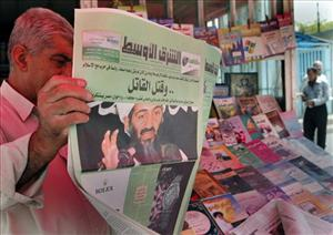 An Iraqi man reads a newspaper about Osama bin Laden's death.