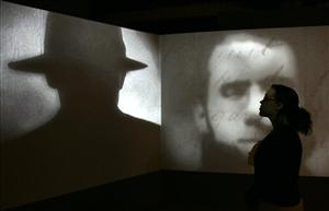 A member of staff stands in front of a screen showing a short movie about Jack the Ripper during a press preview for Jack the Ripper and the East End at the Museum in Docklands, London, May 14, 2008.