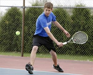 Marshalltown High School sophomore Ethan Lampman, 16, plays tennis near the school, Monday, May 4, 2009. Marshalltown is instituting wake-up calls for chronically late students.